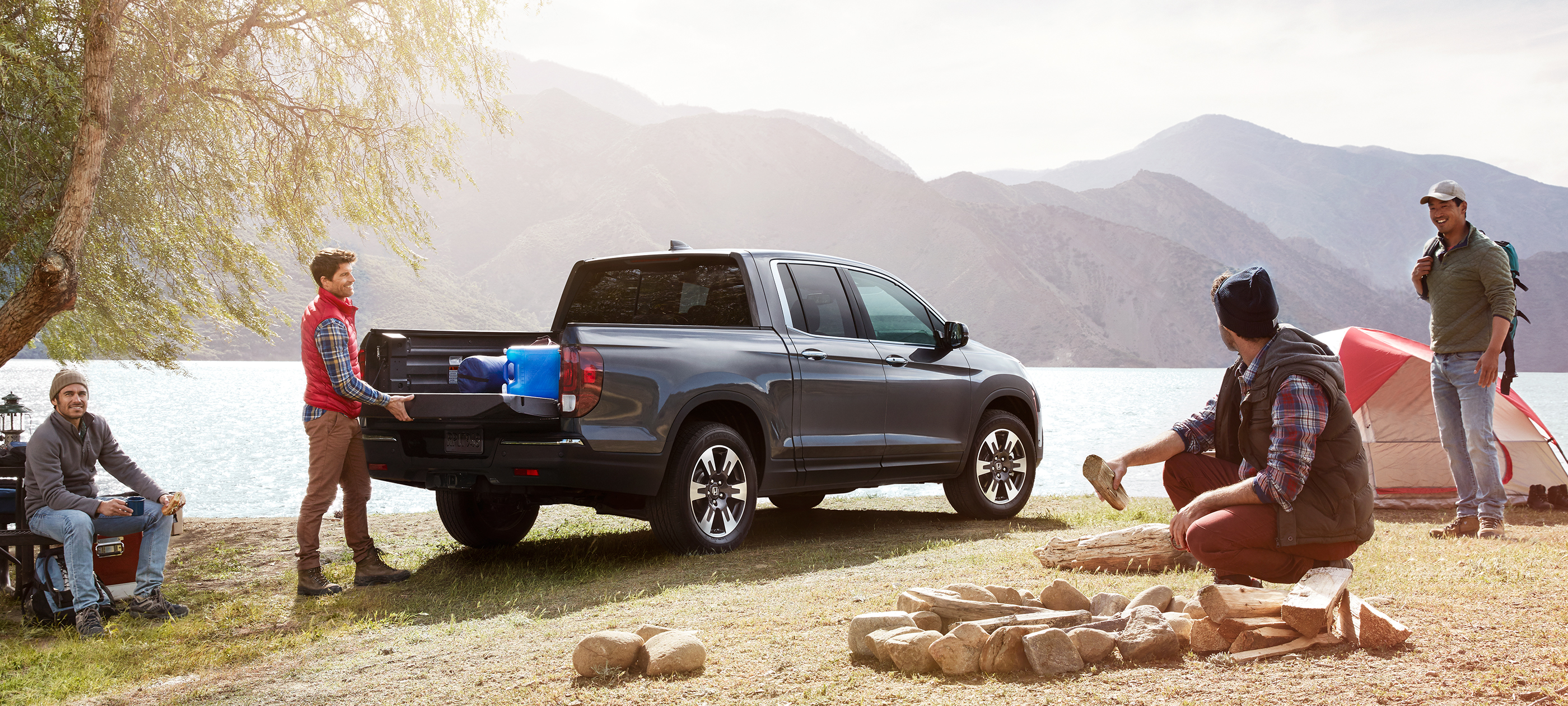 Rear ¾ passenger-side view of 2019 Honda Ridgeline RTL-E in Modern Steel Metallic with tailgate open parked at campsite.