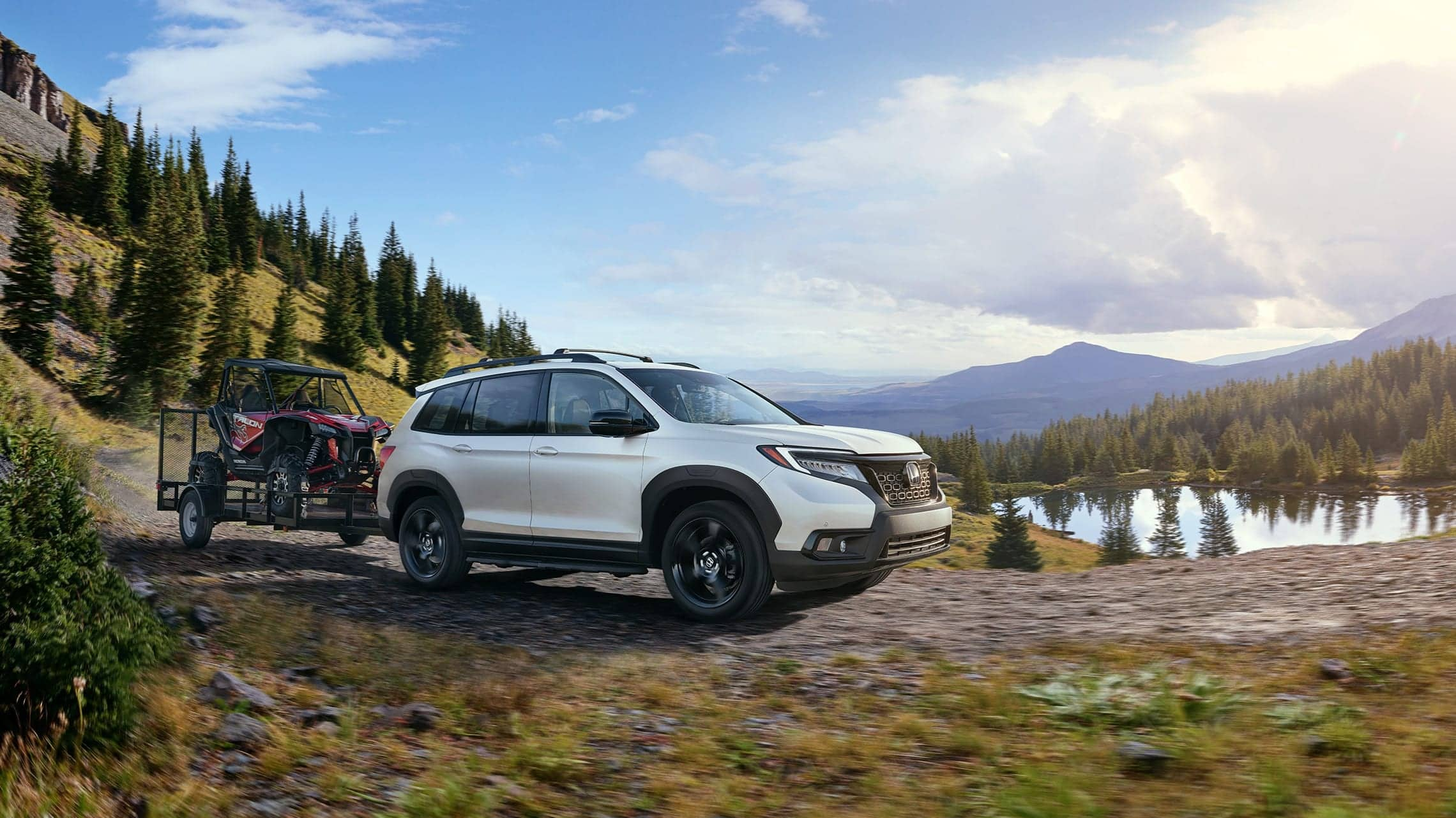 Passenger-side front 7/8 view of 2019 Honda Passport Elite in White Diamond Pearl with accessory tow hitch.