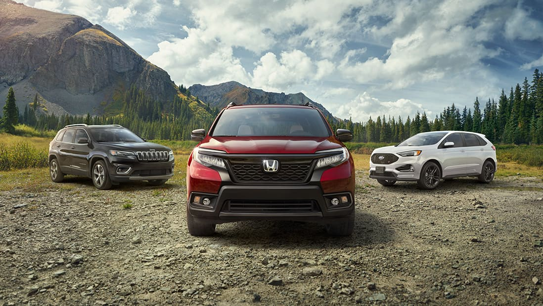 Front view of 2019 Honda Passport in Deep Scarlet Pearl parked on dirt turnout with competitor SUVs and mountains in background