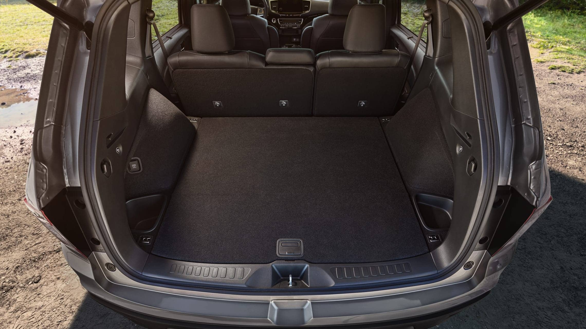 2020 Honda Passport Elite cargo area in Black Leather displaying underfloor storage compartments with carpeted wheel arches.