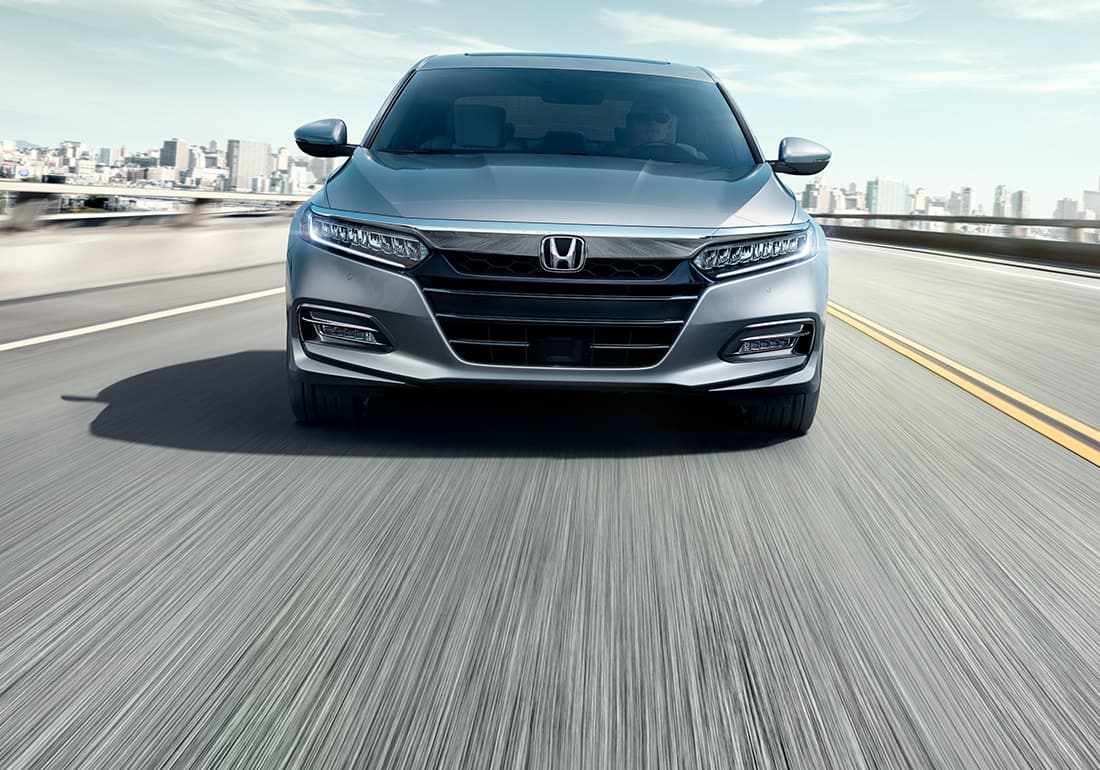 Front view of the 2020 Honda Accord Touring 2.0T in Lunar Silver Metallic driving on highway.