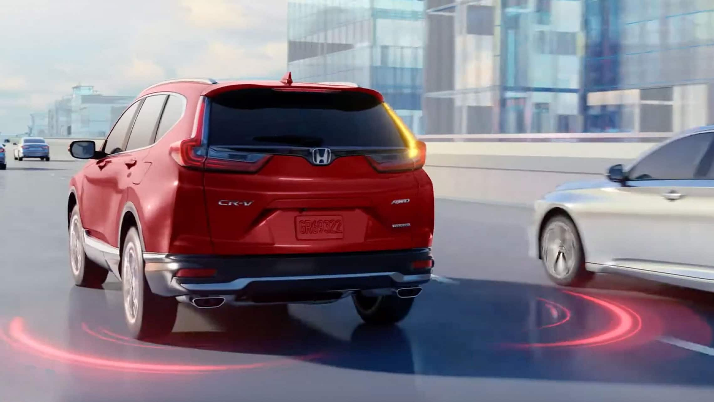 Rear driver-side view of the 2020 Honda CR-V in Radiant Red Metallic, driving on highway, with illustration showing Blind spot information system feature.