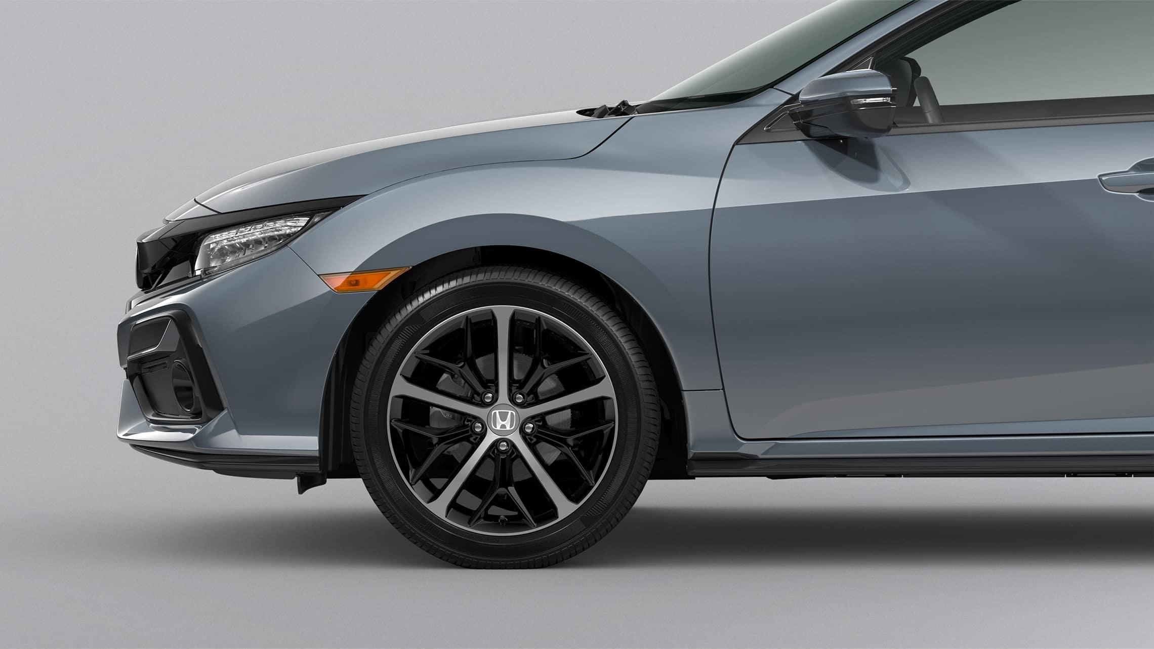 Detalle frontal de ruedas de aleación de 18pulgadas del lado del pasajero en el Honda Civic Sport Touring Hatchback2020 en Sonic Gray Pearl.