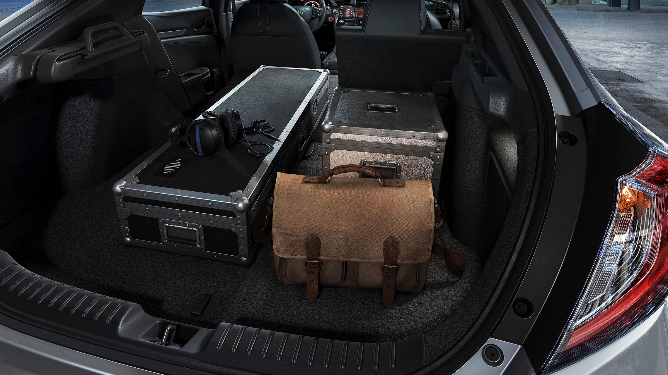 Varios artículos cargados en el espacio de carga del Honda Civic Sport Touring Hatchback2020 con asientos traseros plegables por partes 60/40.