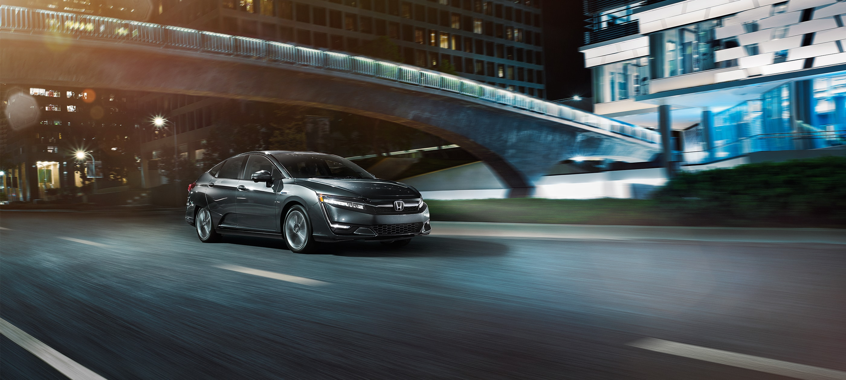 Front ¾ passenger-side view of 2020 Honda Clarity Plug-In Hybrid in Modern Steel Metallic driving on city road at night.