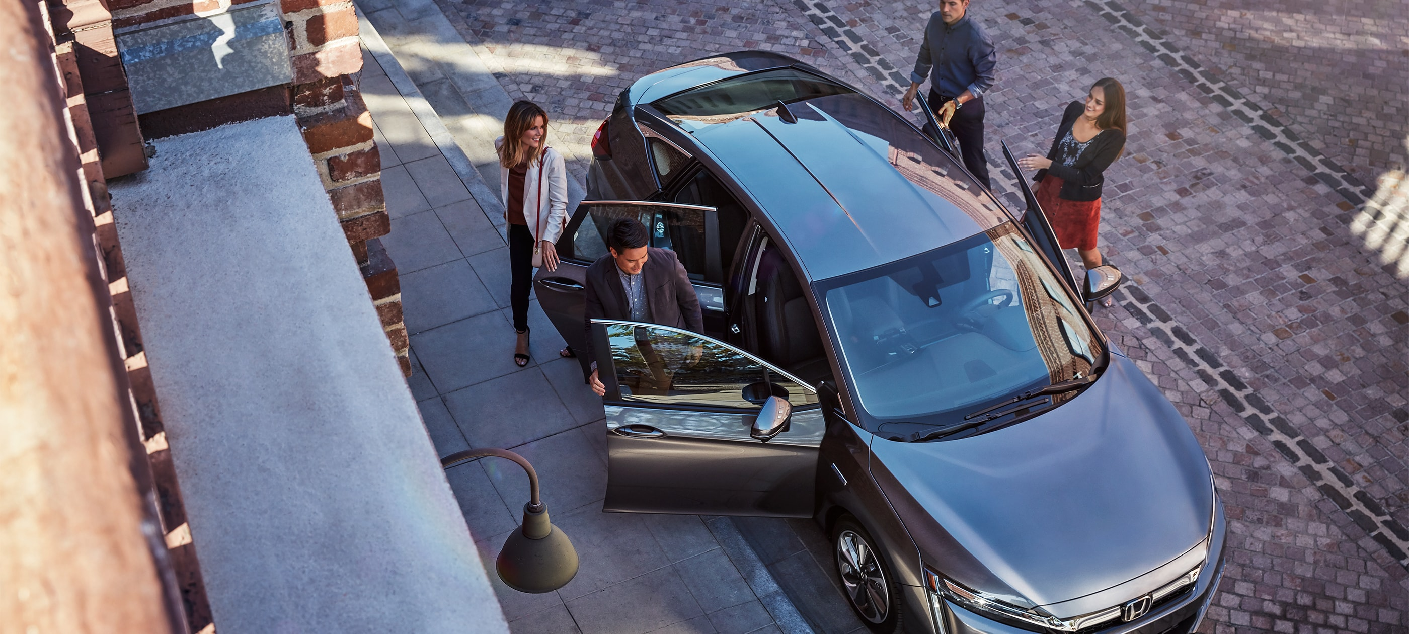 Overhead front ¾ passenger-side view of 2020 Honda Clarity Plug-In Hybrid in Modern Steel Metallic with doors opened for passengers.