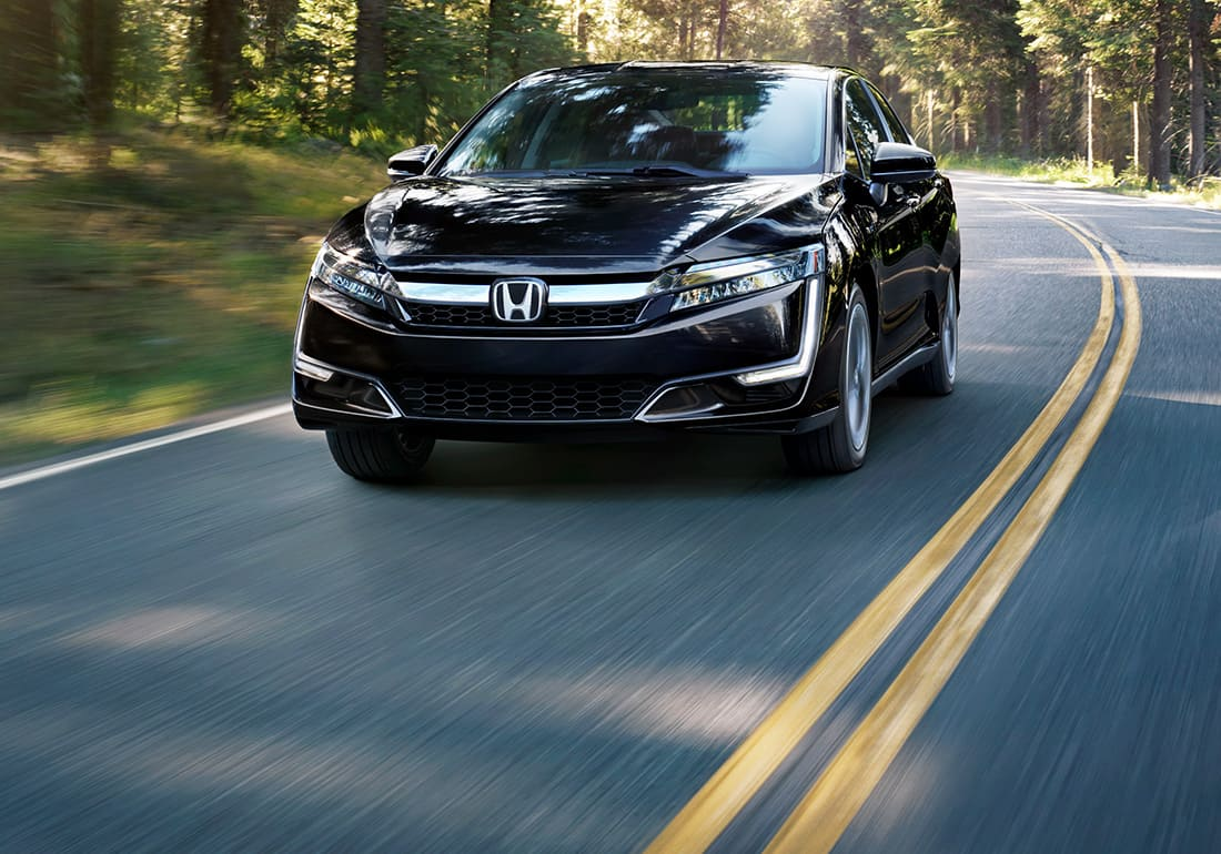 Front ¾ driver-side view of 2020 Honda Clarity Plug-In Hybrid in Crystal Black Pearl driving on forest road.
