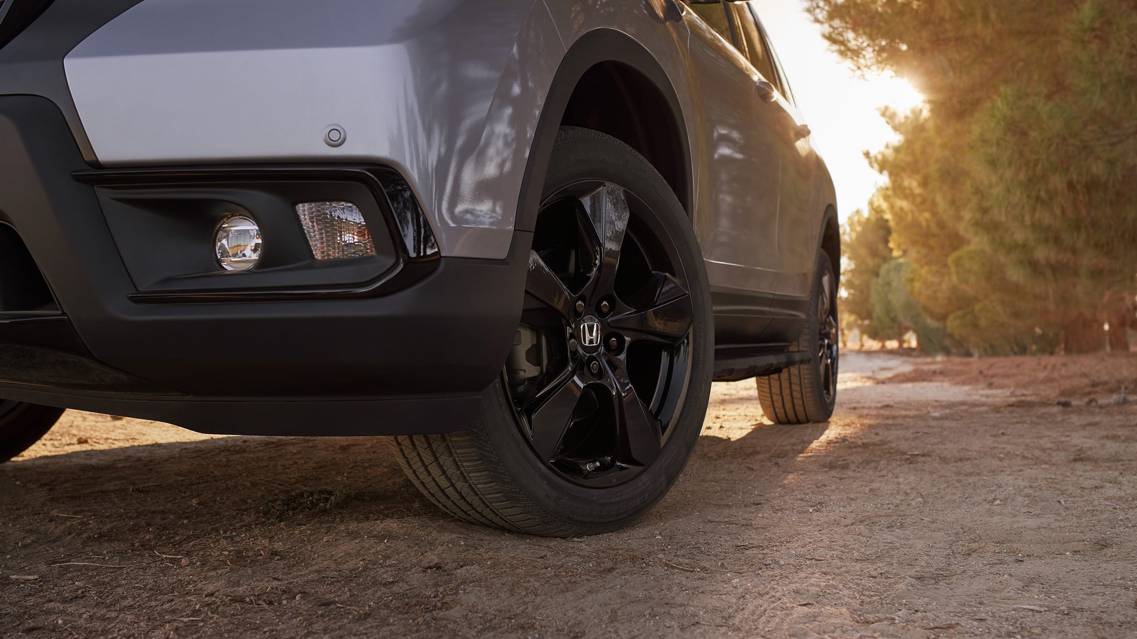 20-inch black alloy wheels on the 2020 Honda Passport Elite, in Lunar Silver Metallic with Honda Genuine Accessories, driving on a rugged road.