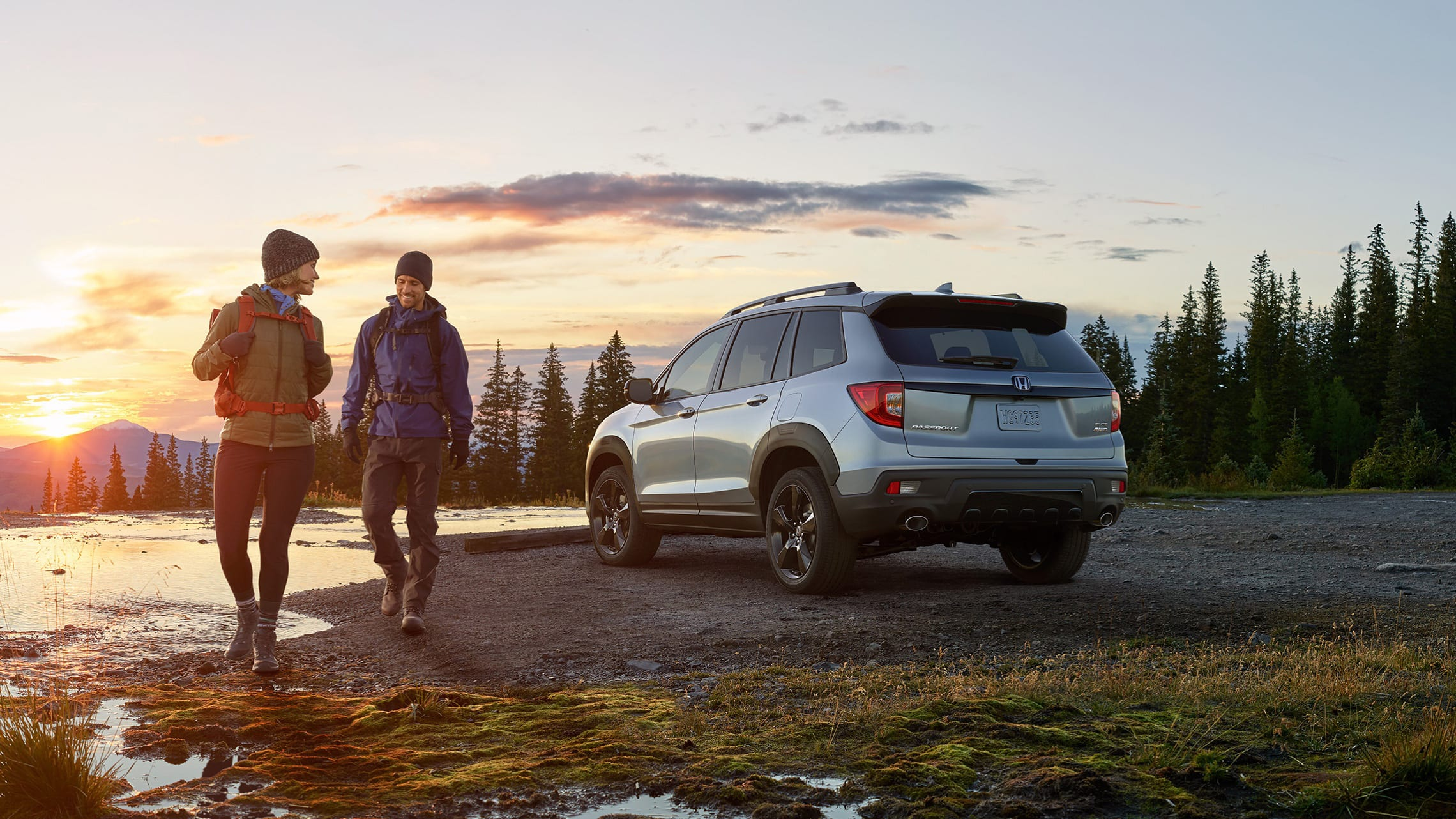 Driver-side 3/4 rear of 2020 Honda Passport Elite in Lunar Silver Metallic with accessory fender flares, at pond location with male and female hikers in foreground.